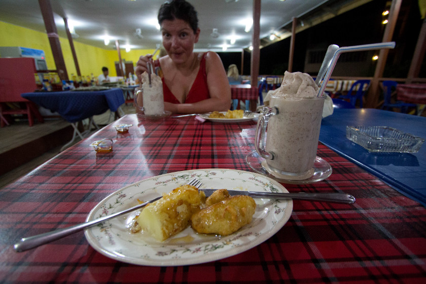Young woman sitting at a table with a thick shake frozen dessert and fried banana